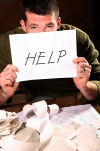 "Man paying bills and holding up ""Help"" sign"
