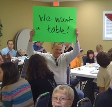 "Man holding up a green sign that says ""We want a table!"""