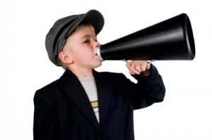 Little boy in a black jacket and hat talking into a black megaphone