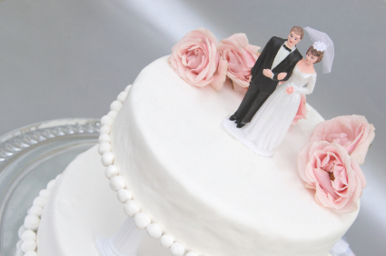 bride and groom atop wedding cake