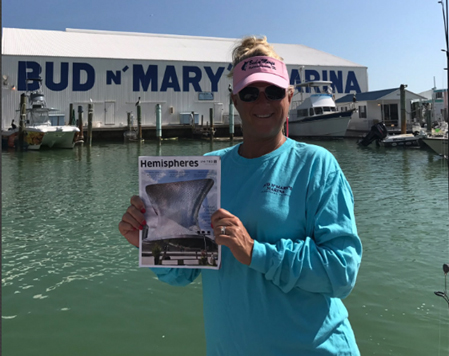Woman holding up magazine at a marina